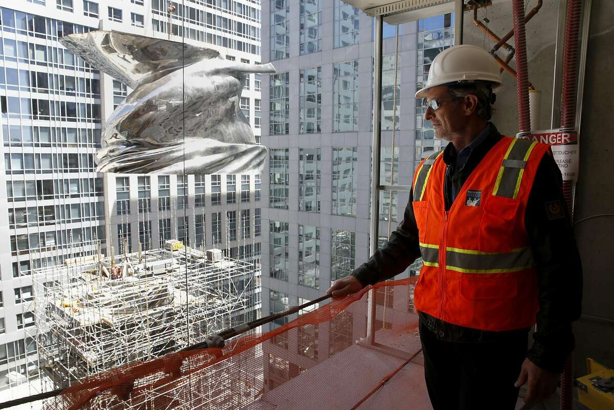 Lawrence Argent watches as crews lift a section of his sculpture