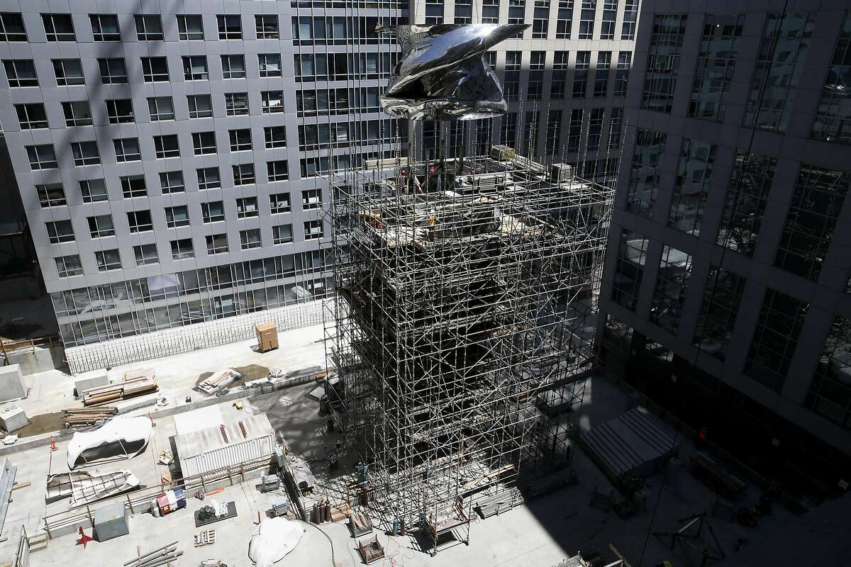 Crews lift a section of the 92-foot-tall sculpture