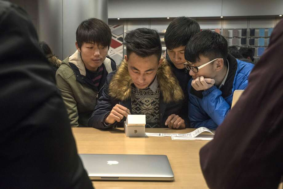 A man sets up his new iPhone 6S at an Apple Store in Beijing. The iPhone market may be shrinking. Photo: GILLES SABRIE, NYT