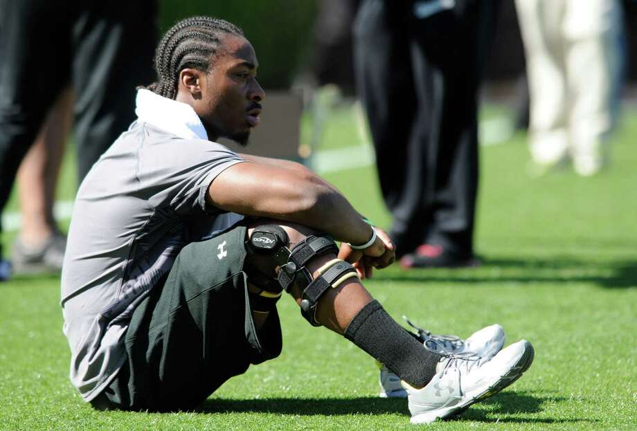 FILE - In this March 27, 2013 file photo, running back Marcus Lattimore looks out on the field before the start of the South Carolina's NFL Pro Day in Columbia, S.C. Three years ago, South Carolina's record-setting running back Marcus Lattimore waited anxiously during the NFL draft to see which _ if any _ team would take a former first-round talent with two seriously damaged knees. Now, Lattimore's awaiting a different goal _ his graduation at from the University of South Carolina on May 6 and the next step in a journey away from the sport he planned to make his career. (AP Photo/Mary Ann Chastain, File) ORG XMIT: NY166 Photo: Mary Ann Chastain / FR170217 AP