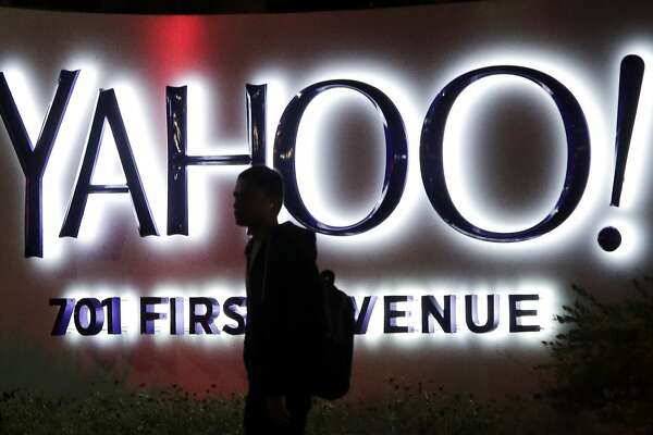 FILE - In this Nov. 5, 2014, file photo, a person walks in front of a Yahoo sign at the company's headquarters in Sunnyvale, Calif. Yahoo reports financial results on Tuesday, April 19, 2016. (AP Photo/Marcio Jose Sanchez, File)