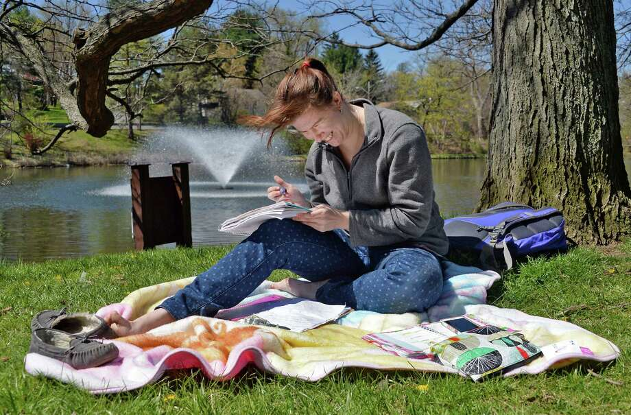 St. Rose student Lily Appleton of East Lyme, Conn., catches some rays as she works on some advanced math homework at Buckingham Lake Thursday April 28, 2016 in Albany, NY.  (John Carl D'Annibale / Times Union) Photo: John Carl D'Annibale / 10036404A