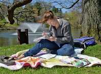 St. Rose student Lily Appleton of East Lyme, Conn., catches some rays as she works on some advanced math homework at Buckingham Lake Thursday April 28, 2016 in Albany, NY.  (John Carl D'Annibale / Times Union)