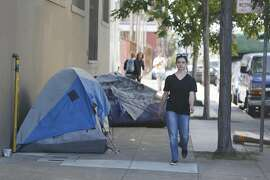 "Vivian Cook of San Francisco walks past tents pitched along Florida Street at 16th Street on Friday, April 29, 2016 in San Francisco, California.  ""It's the criminal activity, I have a problem with; I don't have a problem with the homeless. It's very sad,"" said Kirsty Gumina (not shown), owner McCall Catering and Events, who explained that there had been other homeless who were living on the street outside her business but that there wasn't the criminal activity that there is now. ""There are only two tents today because they just made them move. We're a catering company, we used to feed them. Now  there are car break-ins, hardcore drug use, fighting. I'll walk by and see them shooting up right next to the day care center.  It's become unpredictable and not safe."""
