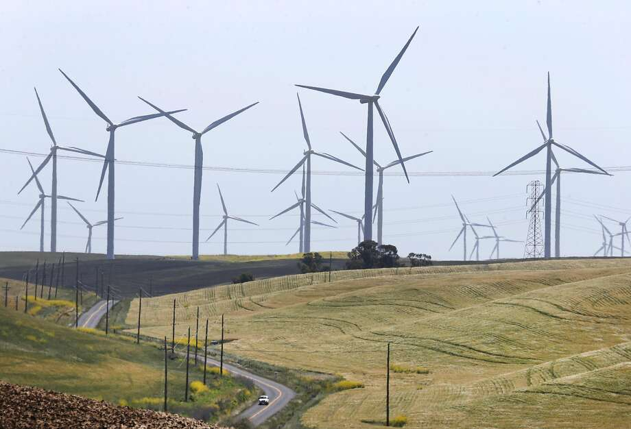 A car drives on Montezuma Hills Road below wind turbines generating power in Birds Landing. CleanPowerSF is now fully operational. Photo: Paul Chinn, The Chronicle