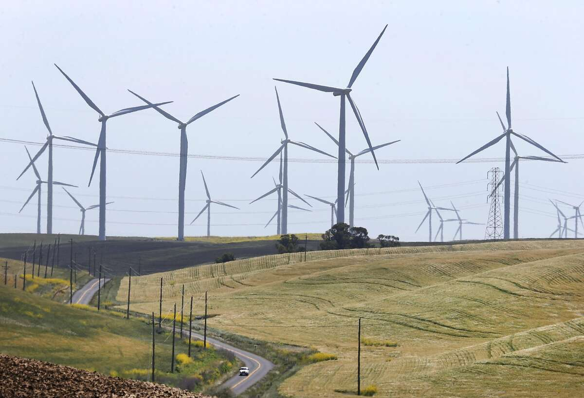A car drives on Montezuma Hills Road below wind turbines generating power in and around the Iberdrola Renewables Shilo wind power farm in Birds Landing, Calif. on Friday, April 29, 2016. The San Francisco PUC's CleanPowerSF program goes fully operational in May.
