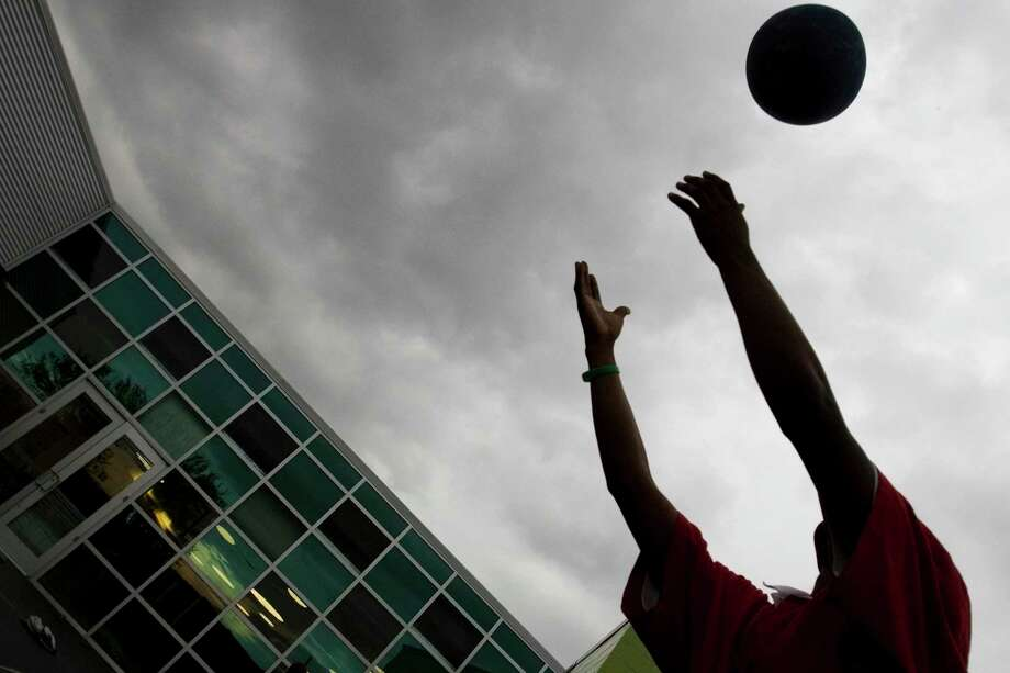 "A client reaches for a ball while playing ""four square"" with others at the Kinder Emergency Shelter, part of the Harris County Youth Services Center in Houston, in 2007. Such facilities are invaluable but part of the foster care fix in Texas must be money for more private foster care providers so children can be cared for in family environments. Photo: SMILEY N. POOL /Houston Chronicle / HOUSTON CHRONICLE"