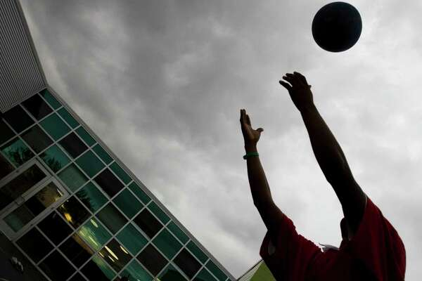 """A client reaches for a ball while playing """"four square"""" with others at the Kinder Emergency Shelter, part of the Harris County Youth Services Center in Houston, in 2007. The foster care system in Texas is under stress, with, according to a court ruling, children leaving the system more damaged than when they came in."""