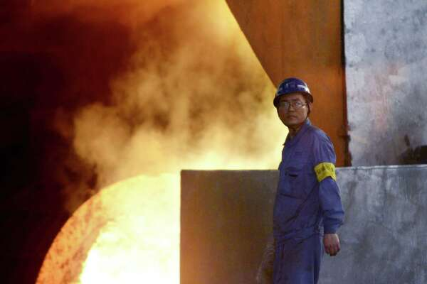 A worker looking on in front of a furnace on April 21 in the Han-steel plant in Handan, in China's northern Hebei province. China's economy expanded at its slowest rate in seven years during the first quarter, the government said on April 15. China has a severely unbalanced economy, with too little consumer spending and unsustainable levels of investment.