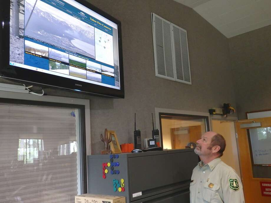 Mac Heller, Camino Interagency Emergency Command Center manager for the Eldorado National Forest and the Lake Tahoe Basin, in his office studying imagery from fire cameras installed around the Tahoe Basin. Photo: Isaac Sims, U.S Forest Service