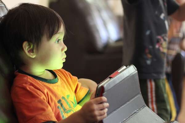 A youngster is learning about using an iPad during Tech Time at the Stepping Stones Museum for Children in Norwalk.