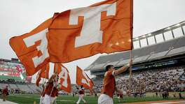 Texas cheerleaders run with flags during the spring football game on April 16, 2016, in Austin.