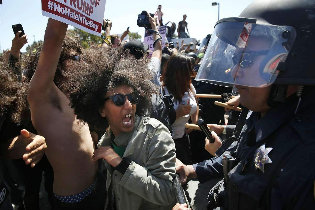 Biseat Yawkal an Oakland protester with BAJI and BLM yells as she is pushed by police as they move protesters back who broke through barriers outside of the Hyatt Regency during the first day of the California Republican Party Convention which featured speeches from Presidential candidates Donald Trump and John Kasich among others April 29, 2016 in Burlingame, Calif.