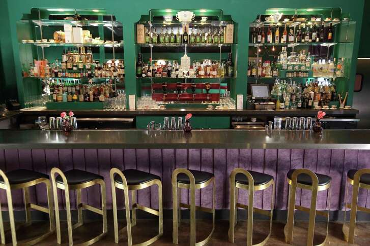 Canard bar, designed by Joel Mozersky Design, is painted deep teal and the bar is padded in purple velvet.