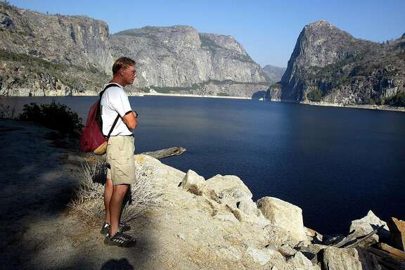 "(NYT31) YOSEMITE NATIONAL PARK, Calif. -- Oct. 14, 2002 -- CALIF-DAM-DISMANTLED -- In the old days, Hetch Hetchy was a breathtaking glacier-carved valley in a newly established Yosemite National park. But an eight-mile ribbon of the valley floor has been buried beneath 300 feet of water since 1913, when the city of San Francisco flooded Hetch Hetchy for a reservoir. Now a group of environmentalists has begun a new effort to turn back what Richard W. Sellars, an author and longtime National Park Servicehistorian, describes as ""the most famous and egregious invasion of a national park.'' Ron Good, executive director of Restore Hetch Hetchy, at the reservoir that he wants to have drained. More than 1,900 acres would be uncovered. (Monica Almeida/The NewYork Times)*LITE"