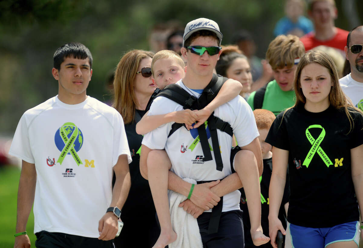 Hunter Gandee carries his brother Braden, 9, across the Michigan State campus as part of his 111-mile walk in Michigan. A reader sees the walk as a symbolic act that celebrates all of humanity.