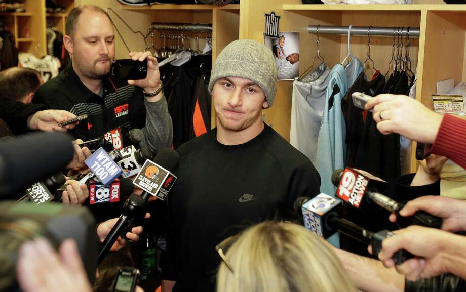 Then-Cleveland Browns quarterback Johnny Manziel talks with the media in 2014 at the NFL football team's training camp, in Berea, Ohio. Johnny Manziel was indicted by a grand jury on Tuesday on misdemeanor charges stemming from a domestic violence complaint by his ex-girlfriend. Photo: Tony Dejak /Associated Press / AP