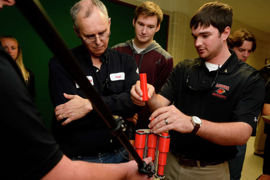 Paul Hall, lead process engineer with ExxonMobil, watches as Matthew Perdue, right, and his teammates demonstrate their Mars rover design system during the senior design symposium for Lamar University engineering students on Friday. The students designed a system to remove soil and rock core samples from the drill and move them to be analyzed.  Photo taken Friday 4/29/16 Ryan Pelham/The Enterprise Photo: Ryan Pelham / ©2016 The Beaumont Enterprise/Ryan Pelham