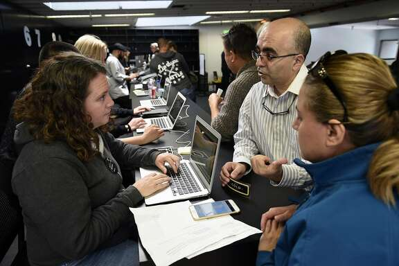 Uber support representative Ellie McHale, left, helps drives Mahone Yesilkaya, and Filiz Aslan with a billing problem on their account at the Uber Partner Support Center in San Francisco, CA, Friday, April 29, 2016.