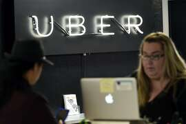A neon Uber sign is seen as support representative Emily Cutlip, right, helps partner driver Luzandra Hucker at the Uber Partner Support Center in San Francisco, CA, Friday, April 29, 2016.