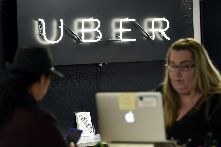 A neon Uber sign is seen as support representative Emily Cutlip, right, helps partner driver Luzandra Hucker at the Uber Partner Support Center in San Francisco, CA, Friday, April 29, 2016. Photo: Michael Short, Special To The Chronicle