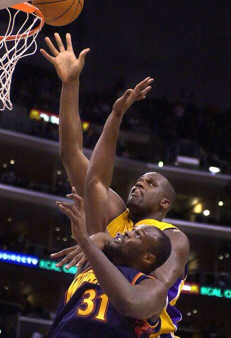 Los Angeles Lakers' Shaquille O'Neal, right, scores over Golden State Warriors' Adonal Foyle during the second quarter Sunday, March 4, 2001, in Los Angeles. O'Neal scored a game-high 26 points in the Lakers'110-95 win. (AP Photo/Kevork Djansezian) Photo: KEVORK DJANSEZIAN, AP
