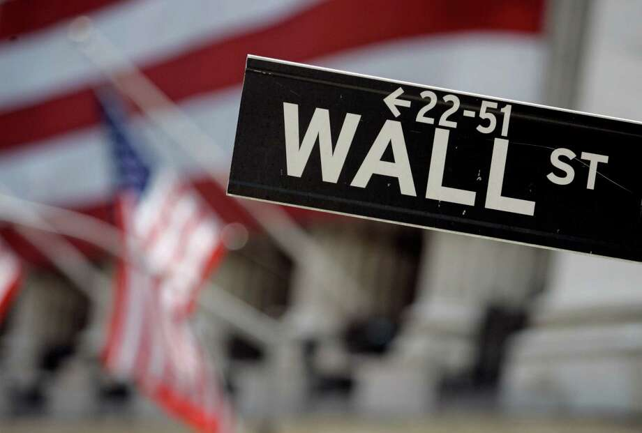 FILE - This May 11, 2007 file photo shows a Wall Street sign in front of the flag-draped facade of the New York Stock Exchange. Global stock markets mostly fell Friday, April 29, 2016,  after Wall Street slid and Japan's central bank surprised markets by putting off possible additional stimulus. (AP Photo/Richard Drew, File) ORG XMIT: NY110 Photo: RICHARD DREW / AP