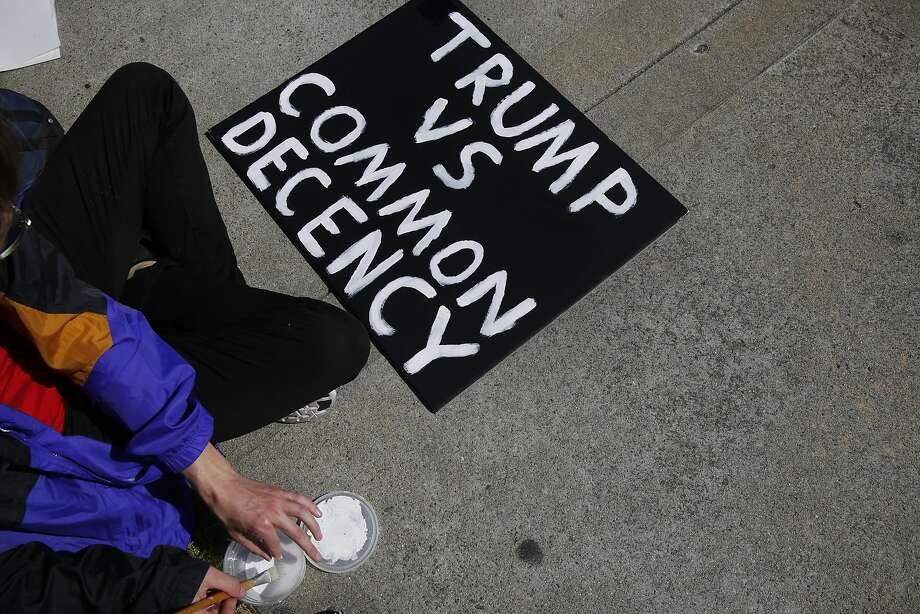 Protester Brandon finishes up painting a sign outside of the Hyatt Regency during the first day of the California Republican Party Convention which featured speeches from Presidential candidates Donald Trump and John Kasich among others April 29, 2016 in Burlingame, Calif. Photo: Leah Millis, The Chronicle