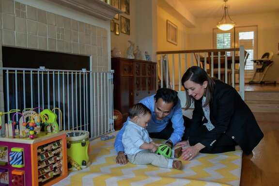 Rob and Natalia Austin play with their son, Brady, in the townhouse they are renting. it's impossible to know whether renting or buying will provide better financial returns over time.