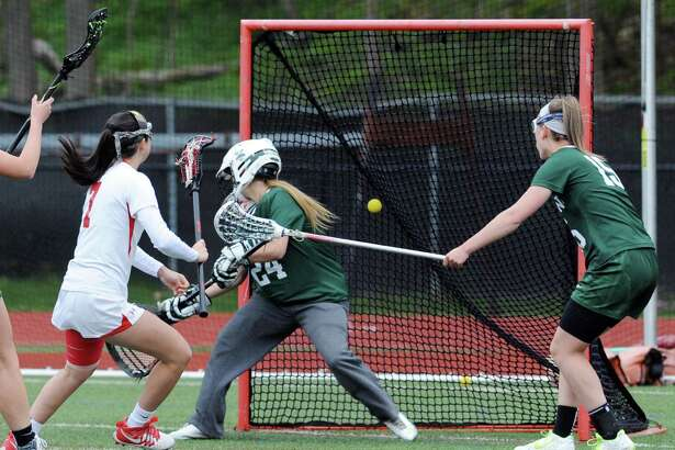 At left, Paige Mautner (#7) of Greenwich scores the third goal of the game as she beats Yorktown goalie Catherine Calidonna while Yorktown's Ashley Stilo (#15), at right, defends during the girls high school lacrosse match between Greenwich High School and Yorktown High School (Yorktown Heights, New York) at Greenwich, Conn., Friday, April 29, 2016. Greenwich won the match over Yorktown by the score of 12-11.