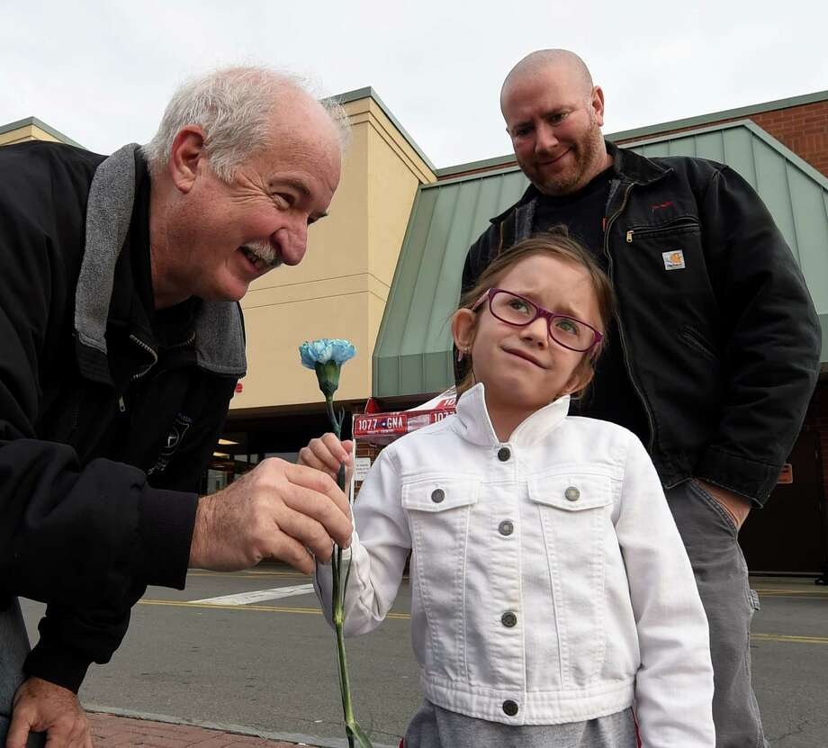 Eight year old Carleigh Flanagan receives a blue carnation from Blue Friday president Pat Fox, left and her dad Dave Flanagan made a donation at the Blue Friday fund raiser April 29, 2016 at the Hannaford Plaza in Colonie, N.Y.     (Skip Dickstein/Times Union) Photo: SKIP DICKSTEIN / 10036400A