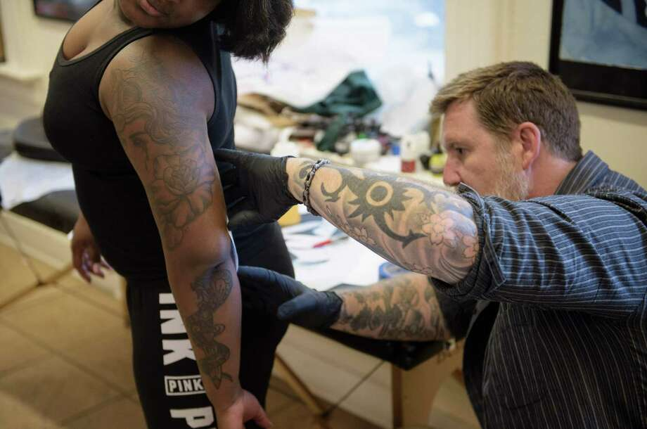 Butch Johnson, owner of Champion Tattoo Company, transfers a tattoo sketch to the arm of U.S. Navy Corpsman Taylor Hoyte on April 18 in Washington, D.C. The Navy has decided to loosen its rules about tattoos in hopes of turning away fewer desired recruits. Photo: BRENDAN SMIALOWSKI, Stringer / AFP or licensors