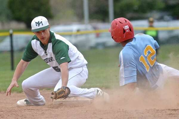 Kolbe's Chris Mojica (12) slides safely into second as New Milford's Timothy Gesauldi (5) turns to make the tag in the boys baseball game between Kolbe Cathedral and New Milford high schools, on Friday, April29, 2016, at New Milford High School, New Milford, Conn.