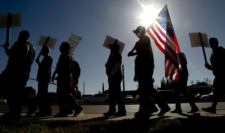 IRVINE, CA - FEBRUARY 10: More than 500 members of the International Brotherhood of Electrical Workers (IBEW) walk the picket line in front of the Southern California Edison building on February 10, 2015 in Irvine, California. The IBEW is supporting the hundreds of IT workers who Edison is laying off in favor of workers in India. (Photo by Mark Boster/Los Angeles Times via Getty Images)