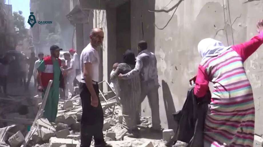 This image made from video released by Qasion News Agency, a media opposition platform that relies on a network of activists on the ground, on Friday, April 29, 2016 shows people scrambling through rubble following airstrikes in Aleppo, Syria. Insurgents shelled a mosque in a government-held neighborhood of Aleppo, killing at least 15 people as they left Friday prayers, while government airstrikes struck rebel-held parts of Syria's largest city — even as the army unilaterally declared a brief truce in other parts of the country. (Qasion News Agency via AP) Photo: UGC