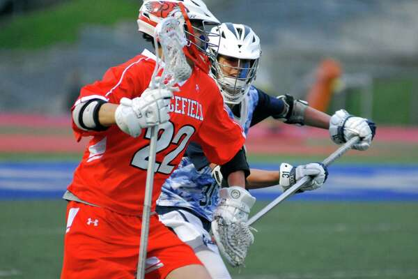 Ridgefield's Mark Galione, left, and Staples' Billy Hutchison battle for position during a boys lacrosse game on Friday, April 29th, 2016.