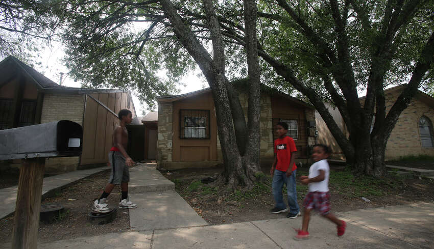 Kids play Friday April 29, 2016 in front of the townhouse at 8105 Chipping where children were allegedly chained up in the back yard. According to the Bexar County Sheriff's Office 8 children were removed from the property and are in the care of Child Protective Services. The case is still being investigated.