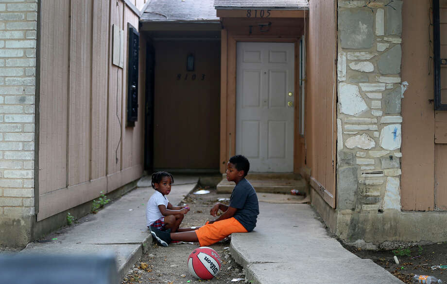 Kids play Friday April 29, 2016 in front of the townhouse at 8105 Chipping where children were allegedly chained up in the back yard. According to the Bexar County Sheriff's Office 8 children were removed from the property and are in the care of Child Protective Services. The case is still being investigated. Photo: John Davenport, Staff / San Antonio Express-News / ©San Antonio Express-News/John Davenport