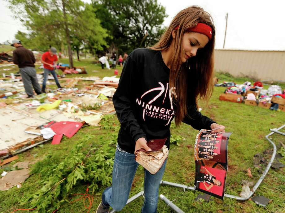 McKenzee Sneed, 14, recovers a team photo and bible as friends and family of her parents Kris and Christeen Allen look for mementos and valuables in the wreckage of their mobil home which was destroyed by storms on Friday, April 29, 2016 in Ninnekah, Okla.   (Steve Sisney/The Oklahoman via AP) Photo: Steve Sisney, MBI / THE OKLAHOMAN