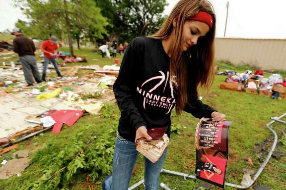 McKenzee Sneed, 14, recovers a team photo and bible as friends and family of her parents Kris and Christeen Allen look for mementos and valuables in the wreckage of their mobil home which was destroyed by storms on Friday, April 29, 2016 in Ninnekah, Okla.   (Steve Sisney/The Oklahoman via AP)