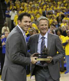 Golden State Warriors head coach Steve Kerr, right, poses for a photo with the league's coach of the year trophy alongside assistant coach Luke Walton before Game 5 of a first-round NBA basketball playoff series Wednesday, April 27, 2016, in Oakland, Calif. (AP Photo/Marcio Jose Sanchez)