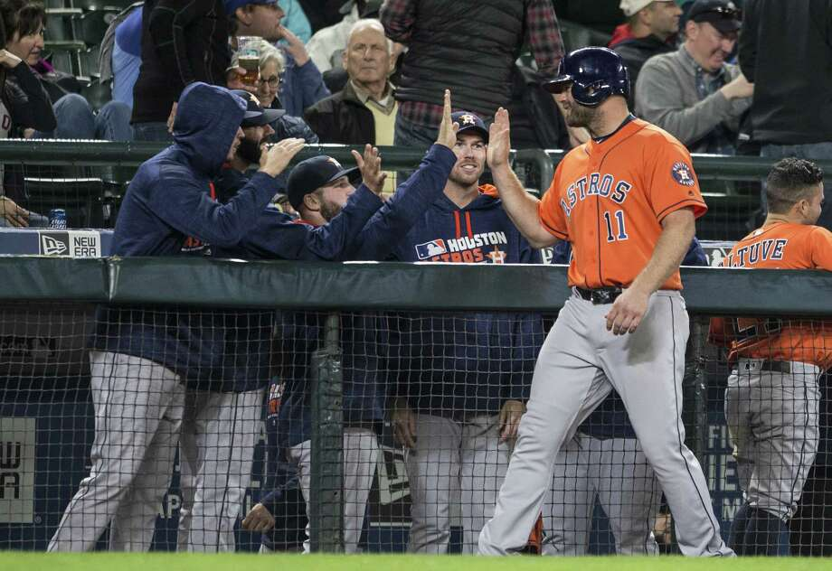 Astros designated hitter Evan Gattis (11) is congratulated by teammates during a break in play after hitting a two-run double during the seventh inning of Wednesday night's game against the Mariners in Seattle. Gattis' double helped the Astros secure a 7-4 victory. Photo: Stephen Brashear, Stringer / 2016 Getty Images