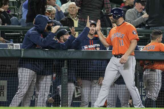 Astros designated hitter Evan Gattis (11) is congratulated by teammates during a break in play after hitting a two-run double during the seventh inning of Wednesday night's game against the Mariners in Seattle. Gattis' double helped the Astros secure a 7-4 victory.