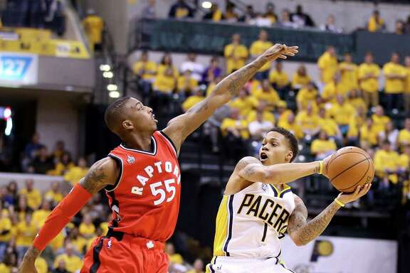 The Pacers' Joe Young, right, looks to pass as the Raptors' Delon Wright tries his best to stop him during Indiana's Game 6 victory Friday night.