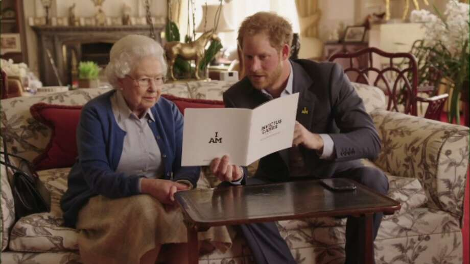 This image taken from a video released by Kensington Palace, London, on Friday April 29, 2016 shows Queen Elizabeth II sitting with her grandson, Prince Harry looking at an Invictus Games brochure. Prince Harry, released the video Friday promoting the upcoming Invictus Games for wounded veterans. The cast includes his grandmother Queen Elizabeth II, and Barack and Michelle Obama, who Harry had over for dinner last week. The video starts with Harry and the queen looking at an Invictus brochure when they get a video phone message from Mrs. Obama. / @KENSINGTONROYAL