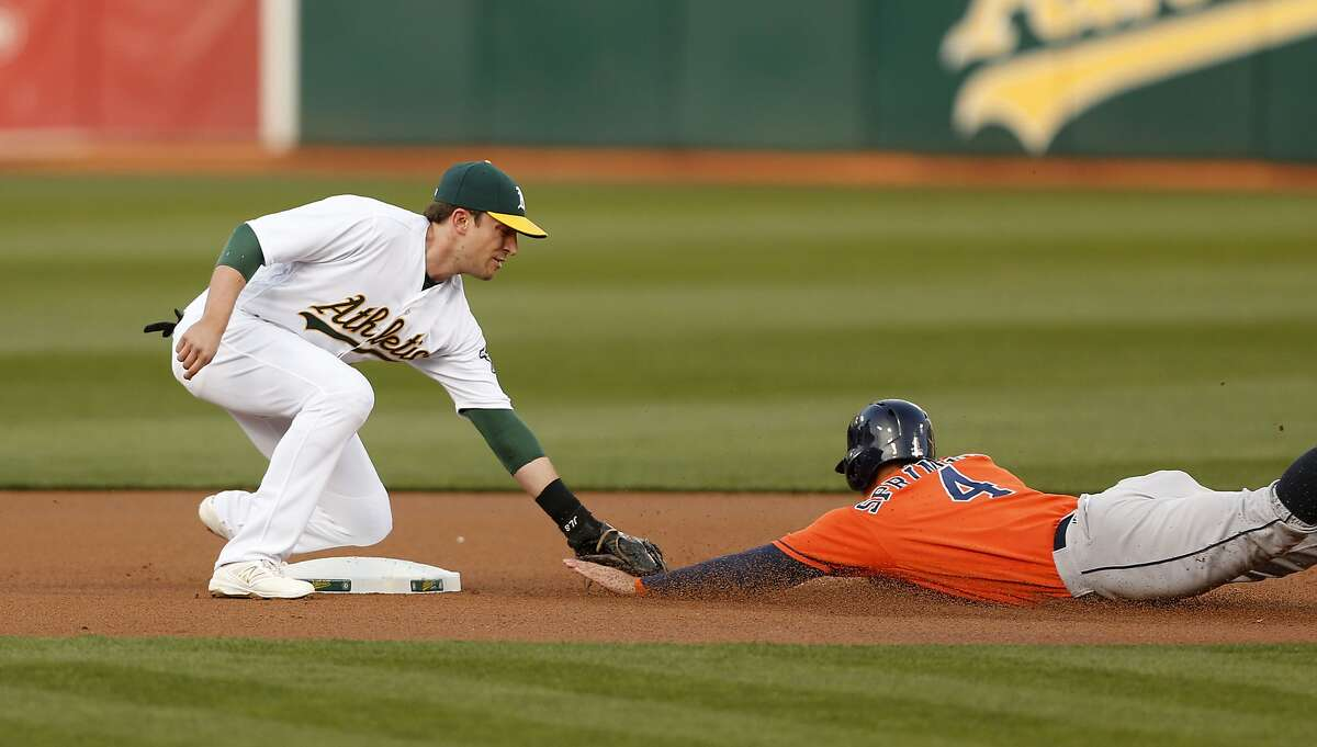 Oakland Athletics second baseman Jed Lowrie catches Houston Astros' George Springer trying to steal second base during the first inning on Friday, April 29, 2016 in Oakland, Calif.