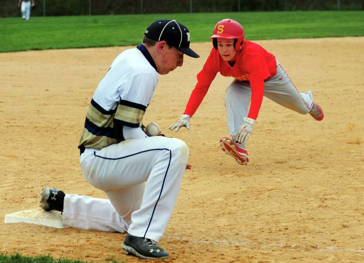 Notre Dame of Fairfield's Bob Karosy bobbles the ball as Stratford's Dan Decilio dives into third during baseball action in Fairfield, Conn., on Friday Apr. 29, 2016. Decilio was called safe.