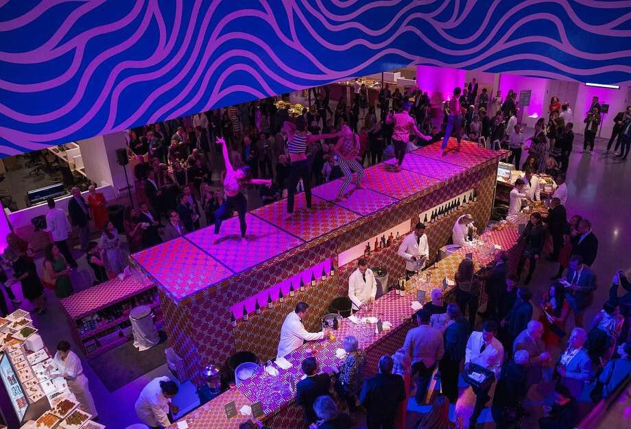 Dancers perform on top of the bar for guests of Art Bash, a party to celebrate the reopening of the San Francisco Museum of Modern Art after it's renovation and expansion, during the event at the museum in San Francisco on Friday, April 29, 2016. The museum opens to the public on May 14. Photo: Laura Morton, Special To The Chronicle