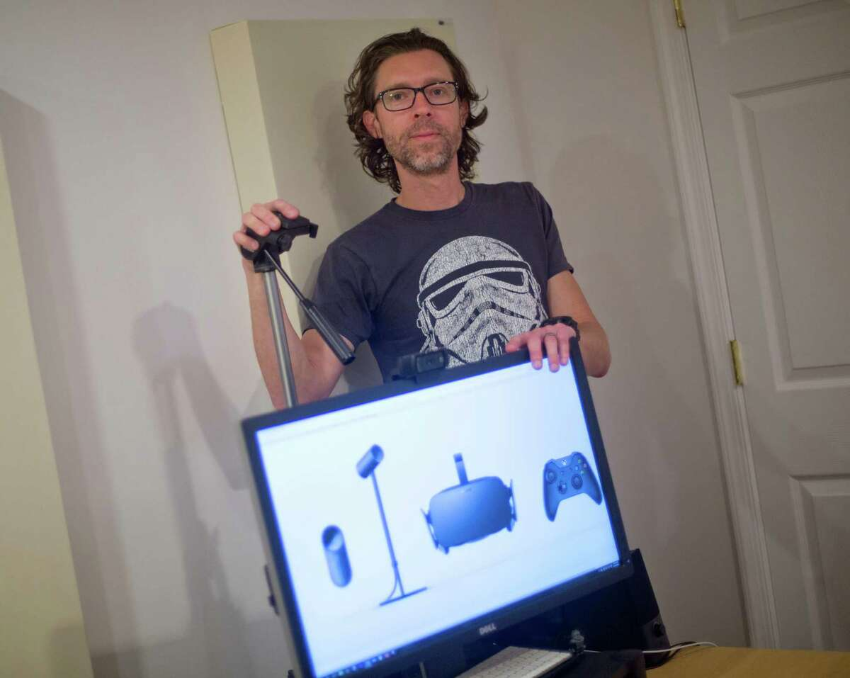 Christian Cantrell, a 42-year-old software engineer and science fiction author, with his high-end computer and tripod set-up that Oculus Rift camera will go with, Friday, April 22, 2016 at his home in Sterling, Va. Cantrell pre-ordered the device, which is shown on the computer monitor, and is still waiting, despite shipping began three weeks ago. (AP Photo/Pablo Martinez Monsivais)