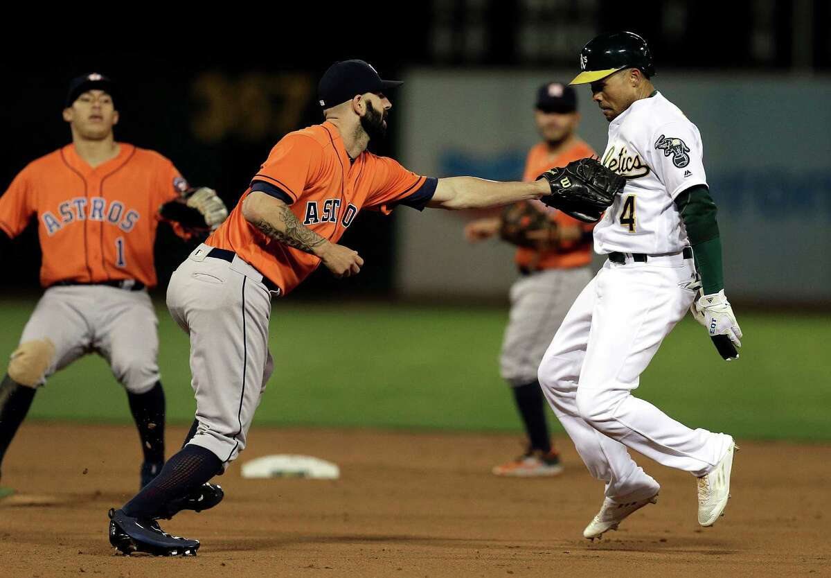 Pitcher Mike Fiers applies the tag after the Astros caught the Athletics' Coco Crisp, right, in a rundown in the fifth inning Friday night.